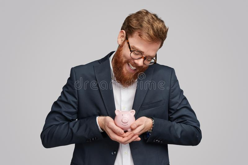 Smiling businessman rocking piggy bank stock images