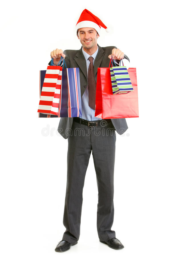 Smiling businessman in Santa hat giving bags stock photography