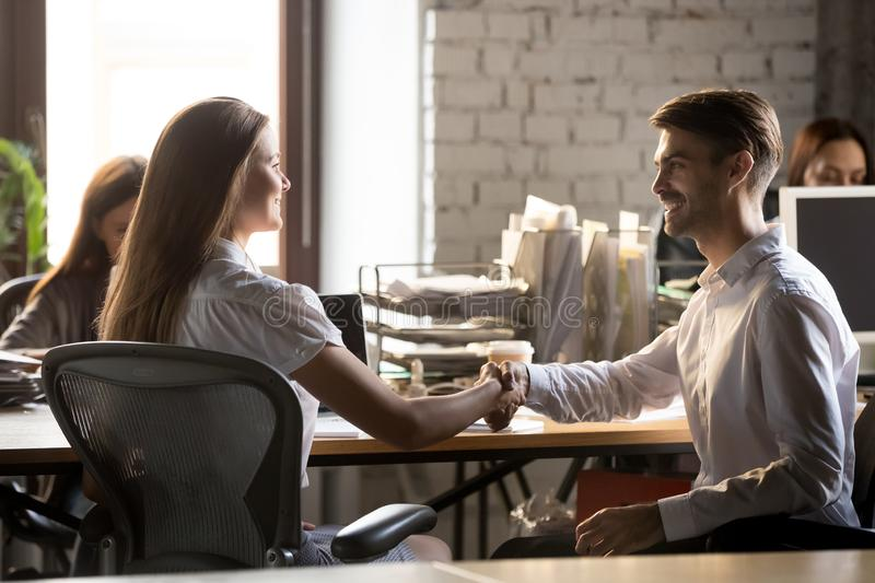 Smiling businessman shaking hand of businesswoman, new colleague stock images