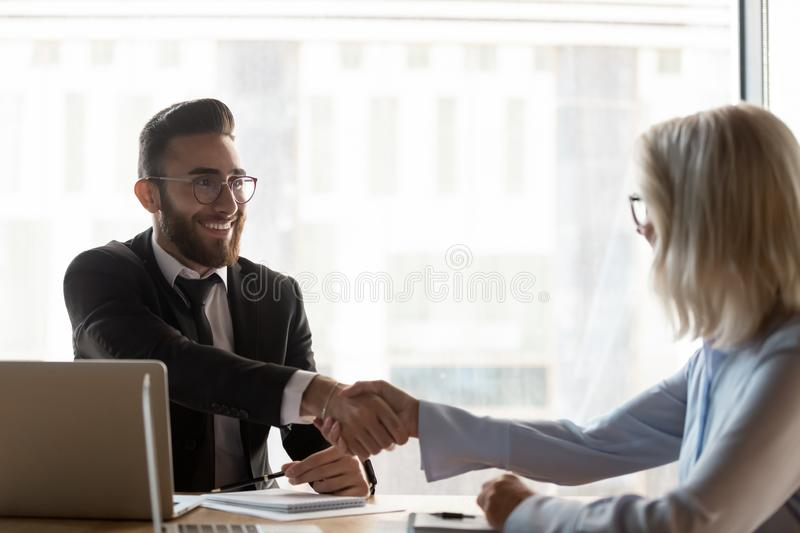 Smiling businessman shaking hand of mature businesswoman at meeting. Business partners greeting each other, successful deal, senior hr manager handshaking with stock photography