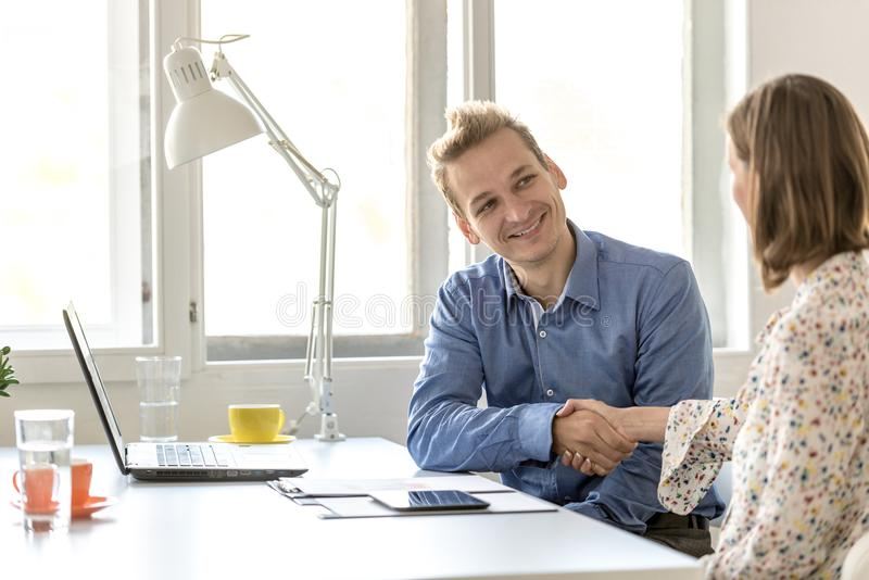 Smiling businessman shaking hands stock image