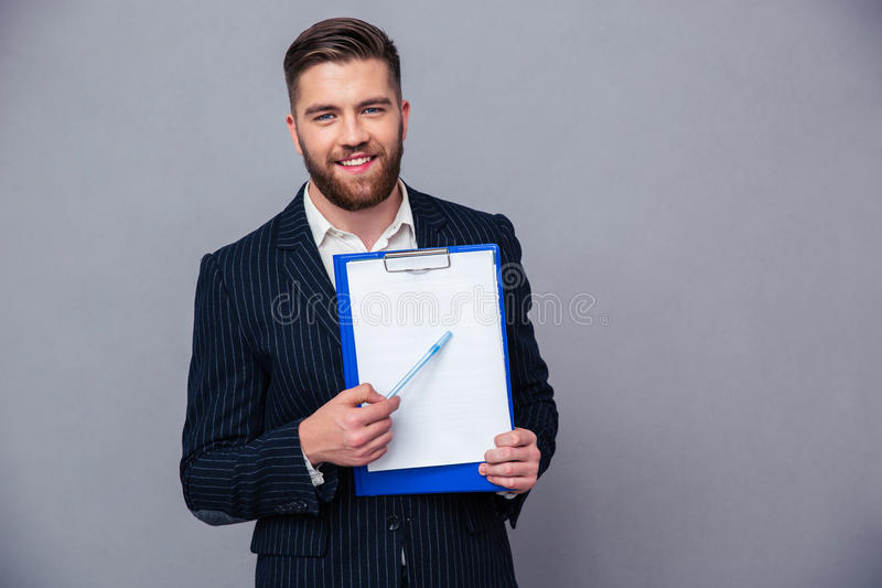 Smiling businessman showing blank clipboard. Portrait of a smiling businessman showing blank clipboard over gray background stock images