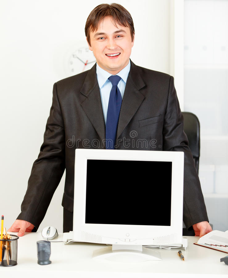 Download Smiling Businessman Showing Monitors Blank Screen Royalty Free Stock Photo - Image: 18414465