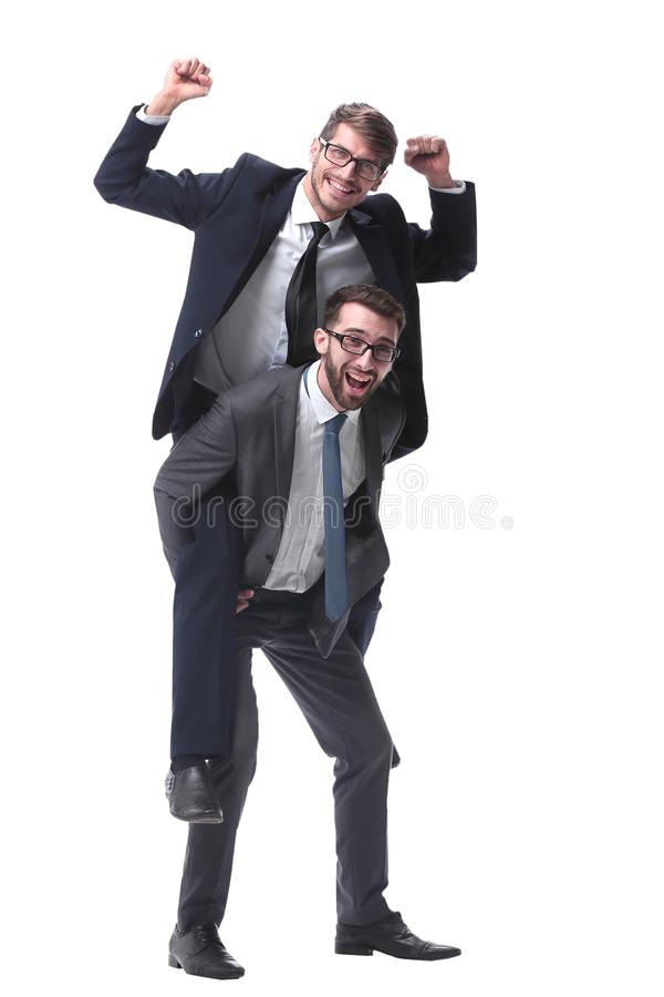 Smiling businessman sitting on the back of his colleague stock photo