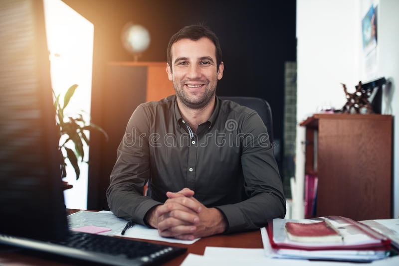 Smiling businessman sitting confidently at his office desk stock photos