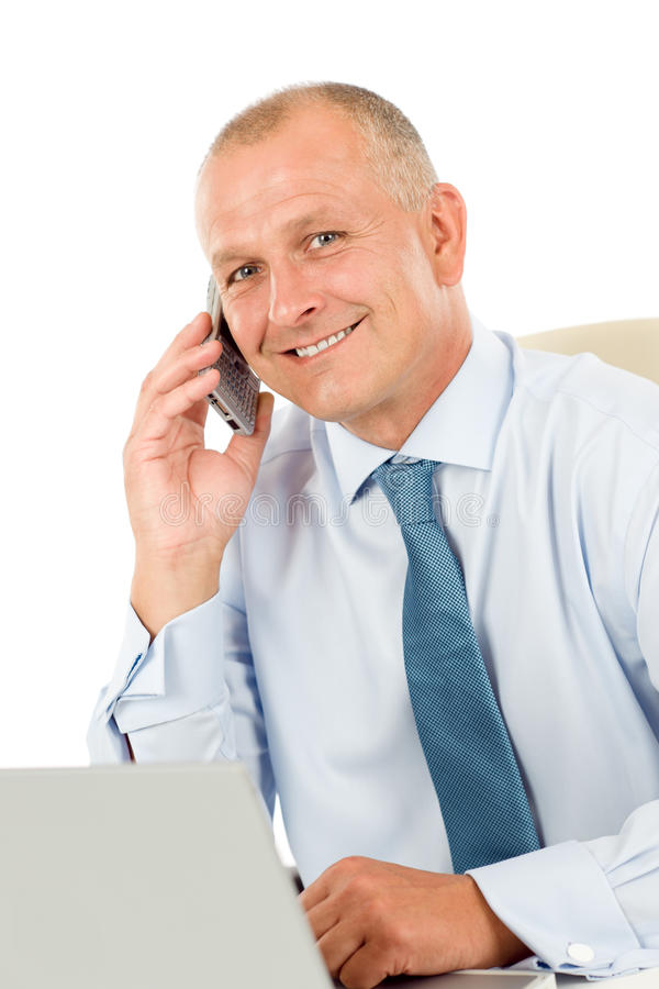 Smiling businessman sitting in office behind desk royalty free stock images