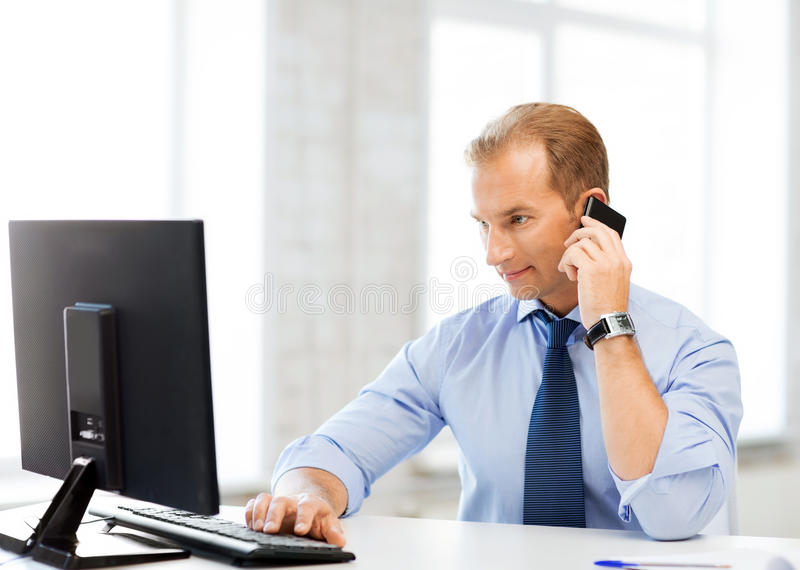 Smiling businessman with smartphone in office stock image