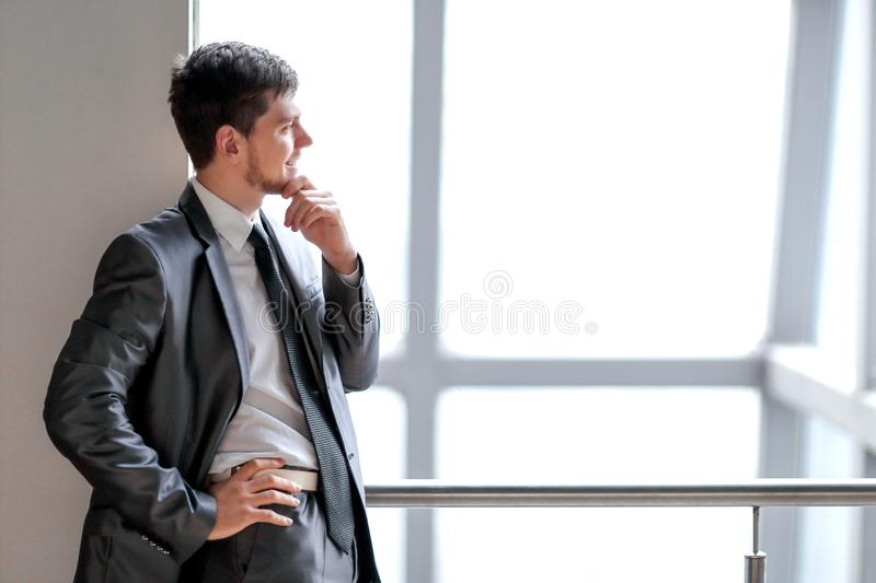 Smiling businessman standing near a large office window royalty free stock images