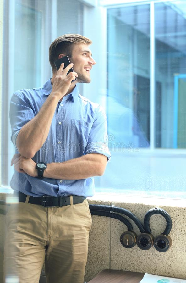 Smiling businessman standing and using mobile phone in office. stock image
