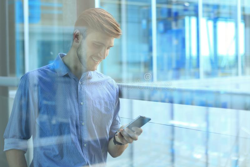 Smiling businessman standing and using mobile phone in office. stock photo