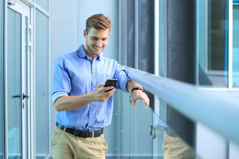 Smiling businessman standing and using mobile phone in office stock photos