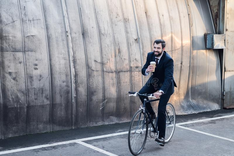 Smiling businessman in suit with coffee to go in hand. Riding bicycle royalty free stock image
