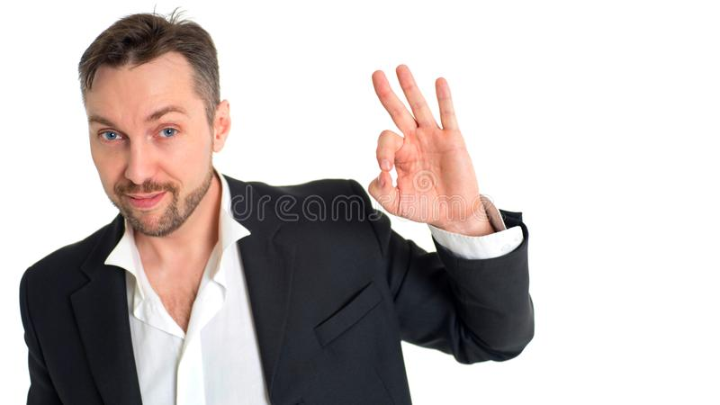 Smiling businessman making alright sign. Smiling businessman in suit making alright sign royalty free stock photos