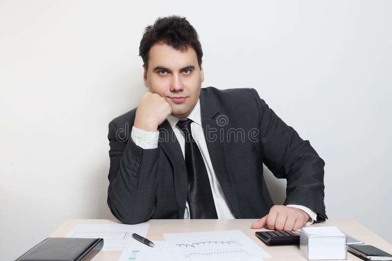Smiling businessman in suit props his chin at table royalty free stock photography