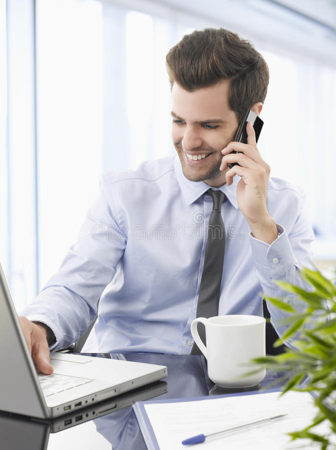 Smiling Businessman Talking On A Mobile Phone. Royalty Free Stock Photo