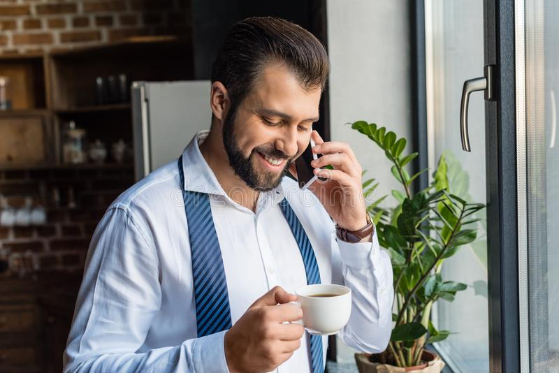 Smiling businessman talking by phone on kitchen with cup. Of coffee stock photos