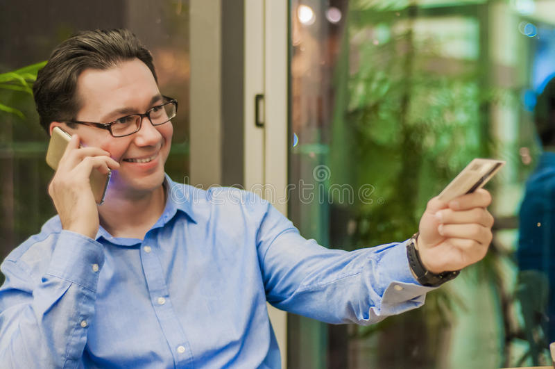 Smiling Businessman talking with smart phone and Giving Card to Waiter in Cafe.  stock photography