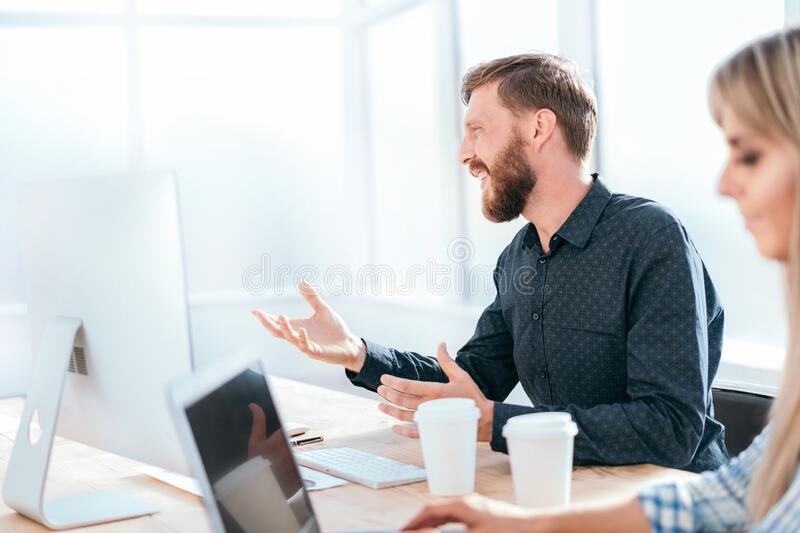 Smiling businessman talking to a colleague sitting at his Desk royalty free stock images