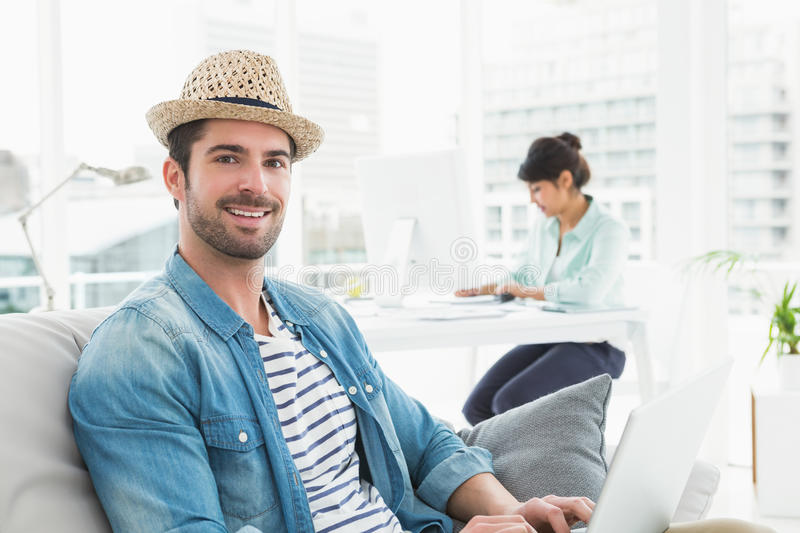 Smiling businessman typing on laptop on couch. With colleague behind him stock image