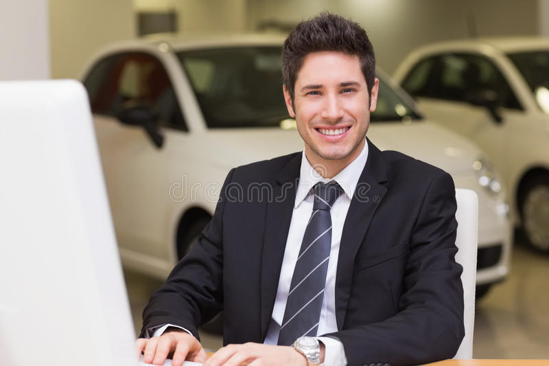 Smiling businessman using a laptop stock image