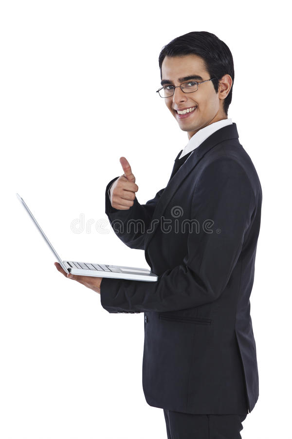 Smiling businessman using a laptop royalty free stock photo