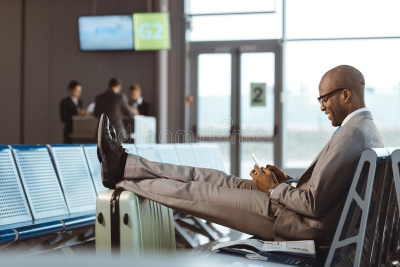 smiling businessman using smartphone while waiting for flight royalty free stock photos