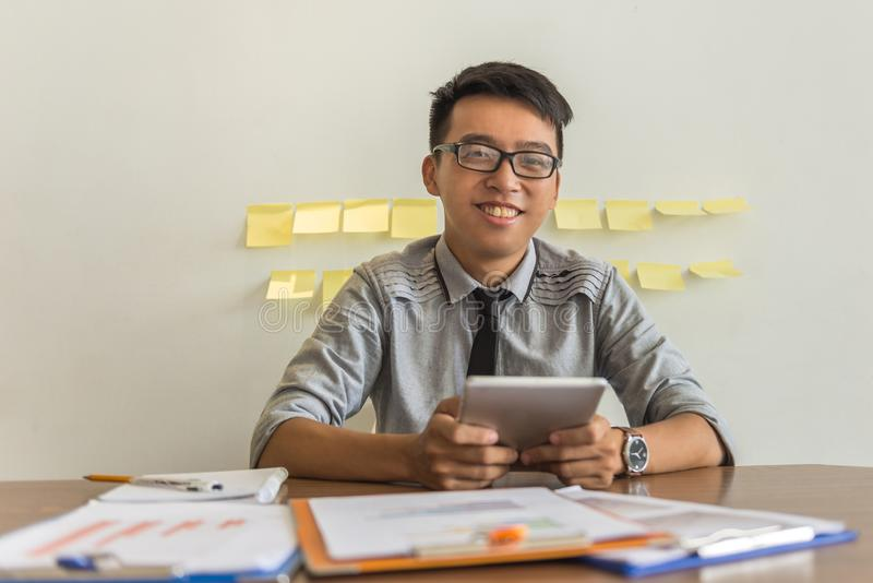 Smiling businessman using tablet in the office royalty free stock images