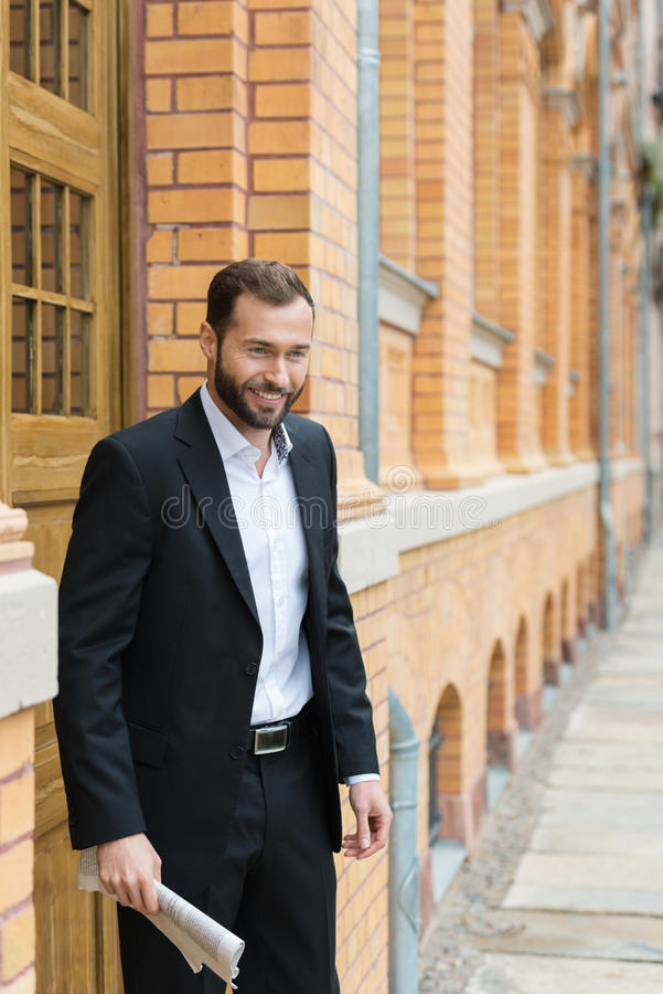 Smiling businessman waiting outside the office royalty free stock photo