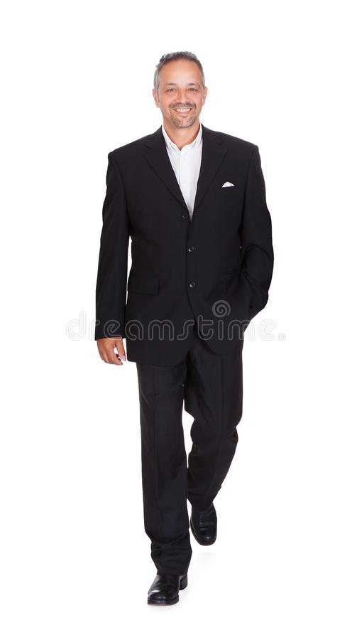 Smiling Businessman Walking Over White Background royalty free stock images
