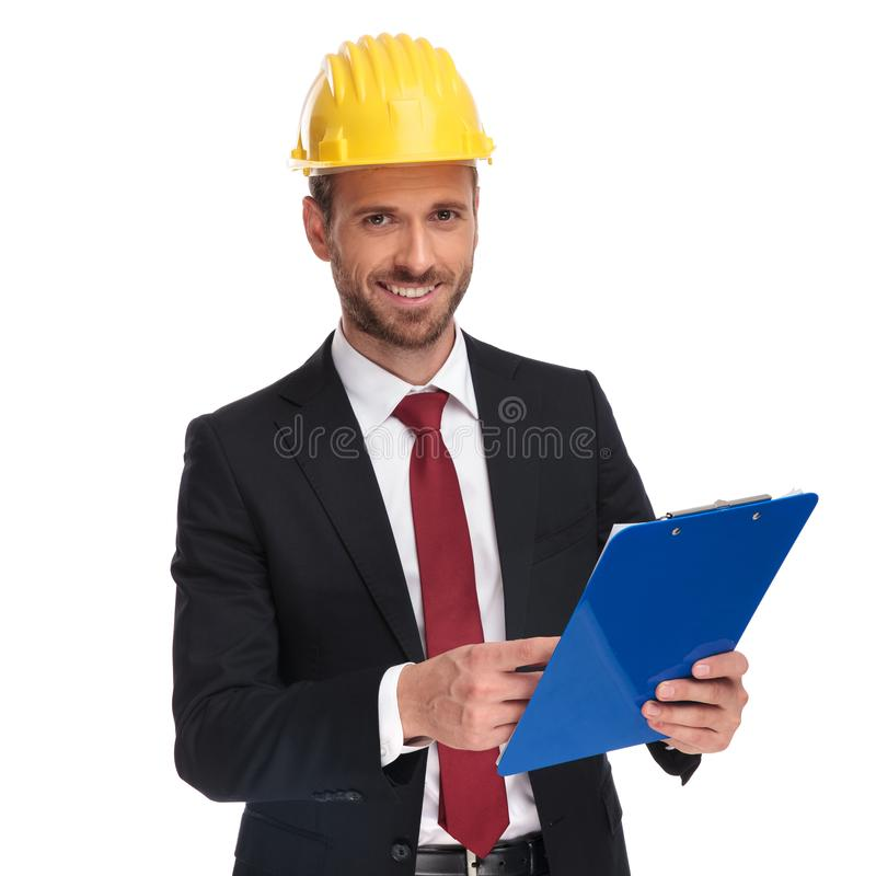 Smiling businessman wearing a protection helmet holds blue files stock photo