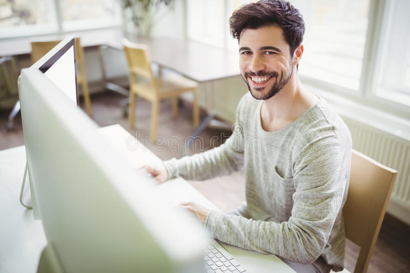Smiling businessman working at desk in office stock images