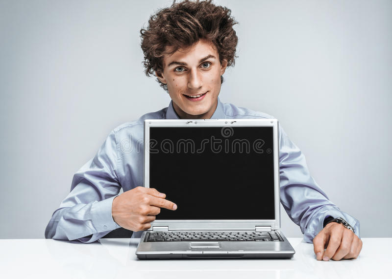 Smiling businessman at the workplace looking at camera. And showing at screen laptop. Business concept royalty free stock photos