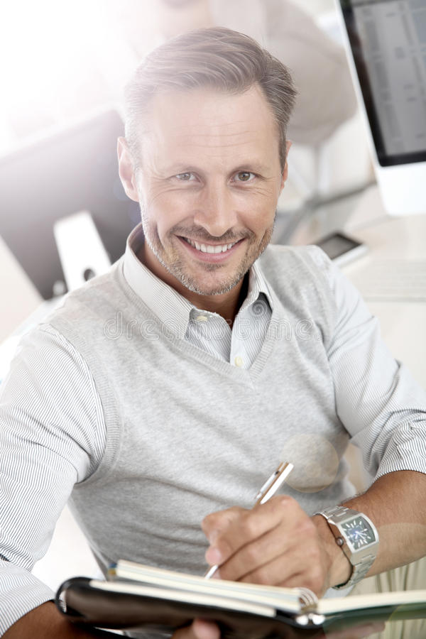 Smiling businessman writing down notes royalty free stock photo