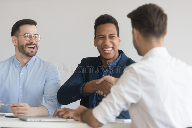 Smiling businessmen handshake getting acquainted at meeting. Excited male colleagues sit at office desk shake hand get acquainted at meeting, smiling men royalty free stock image