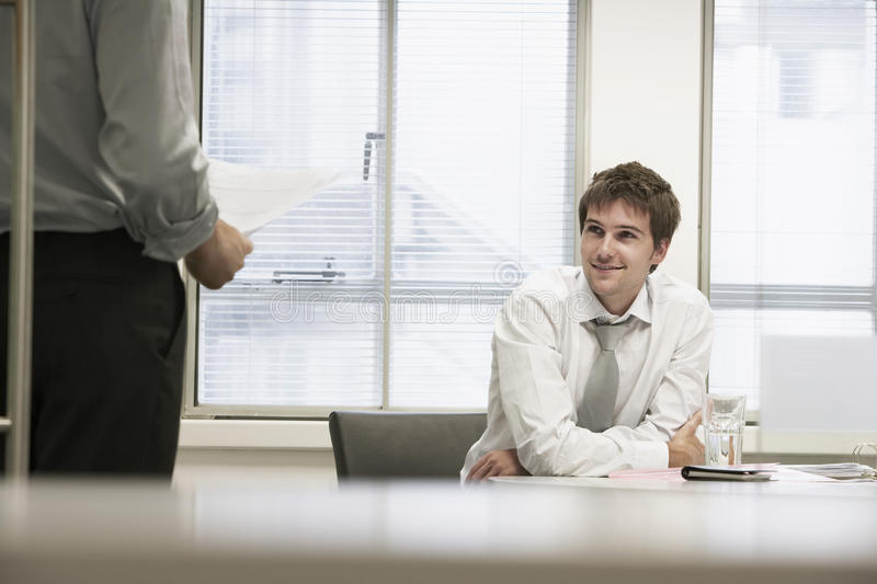 Smiling Businessmen Listening To Male Colleague. Smiling businessmen sitting in office chair and listening to male colleague stock photography