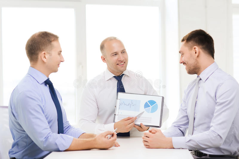 Smiling businessmen with papers in office. Business and office concept - smiling businessman showing others charts in office royalty free stock photos