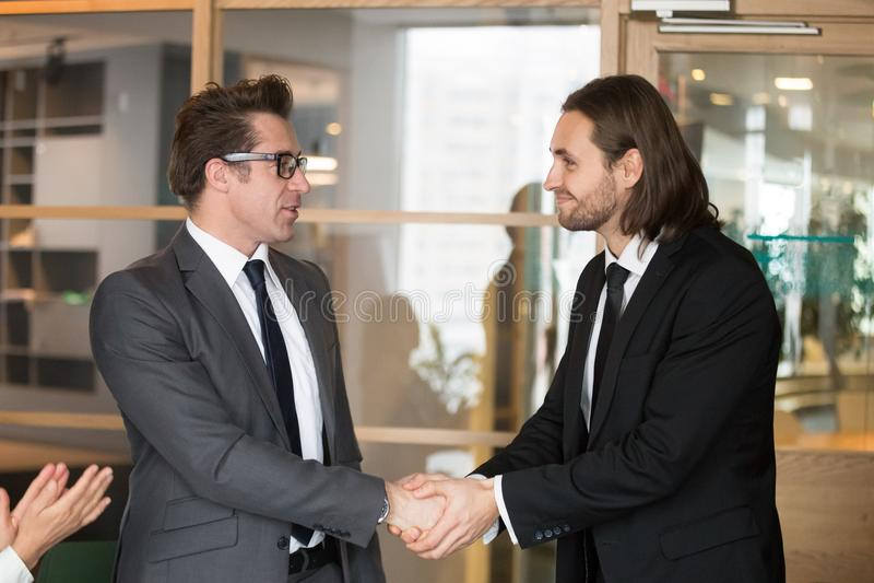 Smiling businessmen shaking hands, making deal, gratitude or pro. Smiling businessmen in suits shaking hands as concept of business deal, expressing gratitude stock images