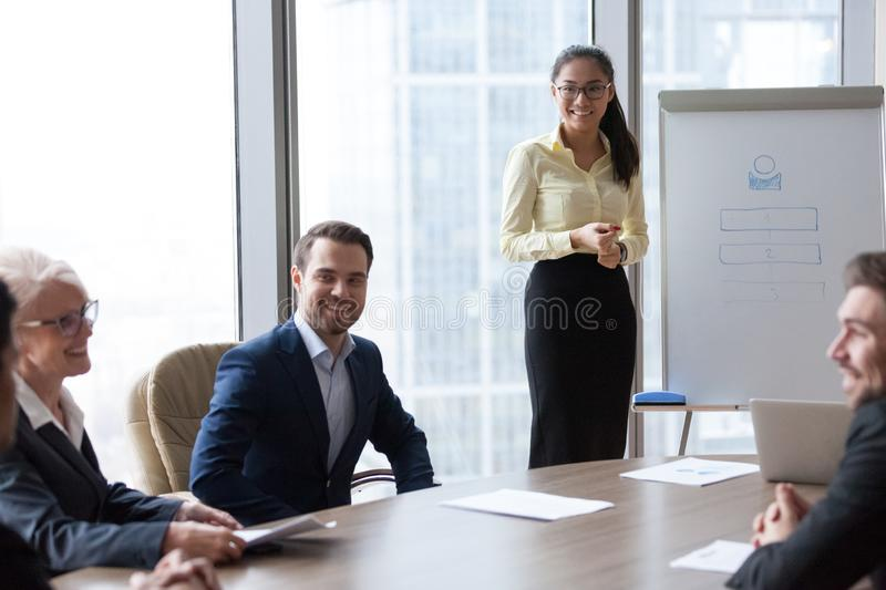 Smiling businesspeople listen asian coach woman at meeting royalty free stock photo