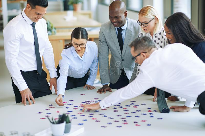 Smiling businesspeople solving a jigsaw puzzle in an office stock photo