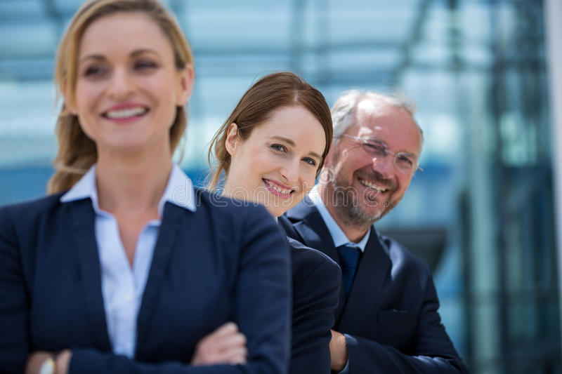 Smiling businesspeople standing with hands crossed royalty free stock image