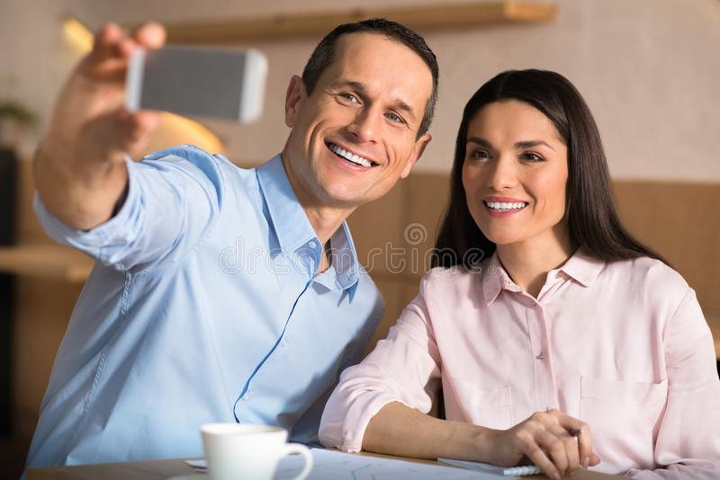 Businesspeople taking selfie on smartphone. Smiling businesspeople taking selfie on smartphone in cafe stock photography