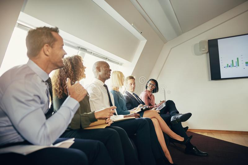 Smiling businesspeople watching a presentation in an office stock photography