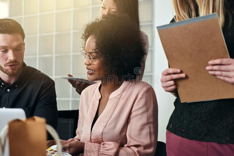 Smiling businesspeople working together at an office desk stock photo