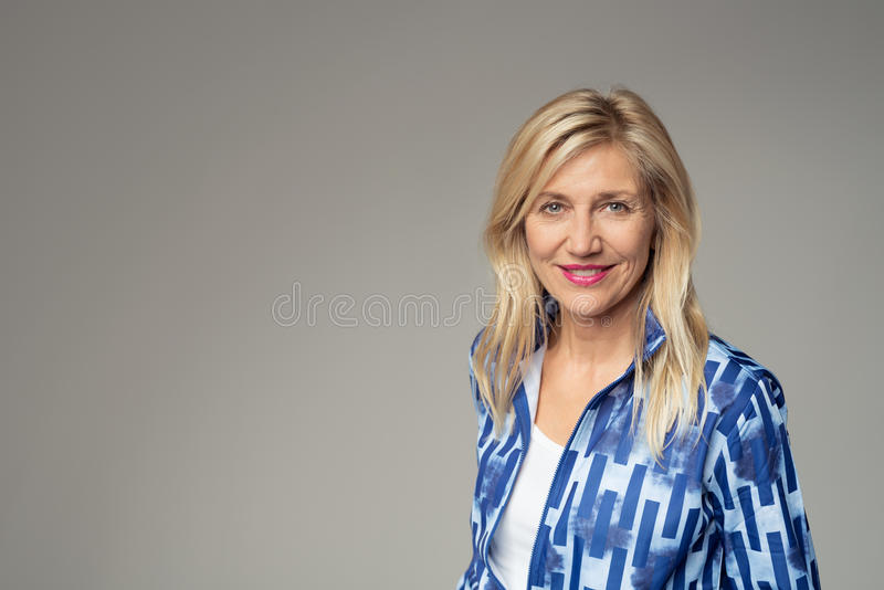 Smiling Businesswoman Against Gray with Copy Space stock photos
