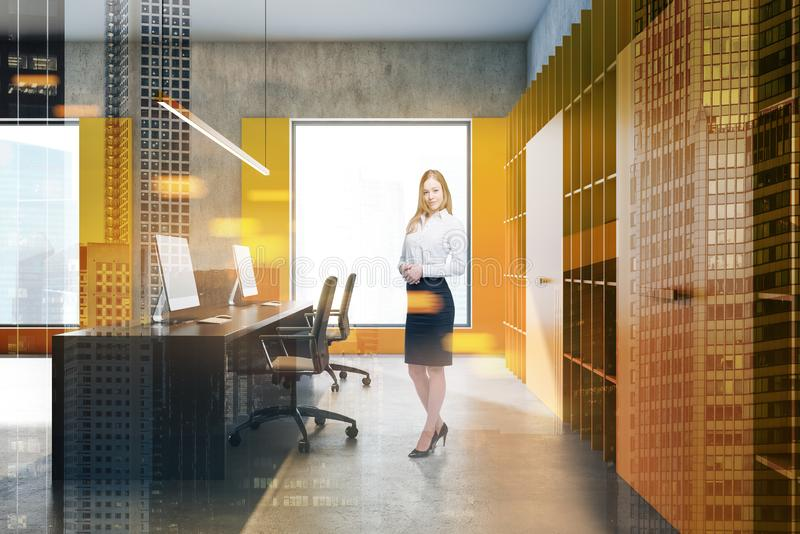 Smiling businesswoman in bright loft office. Smiling blonde businesswoman standing in modern loft office with yellow walls, bookcases and long computer table stock image