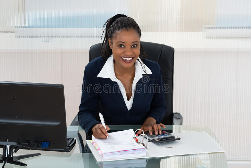 Smiling Businesswoman Calculating Bills royalty free stock photo