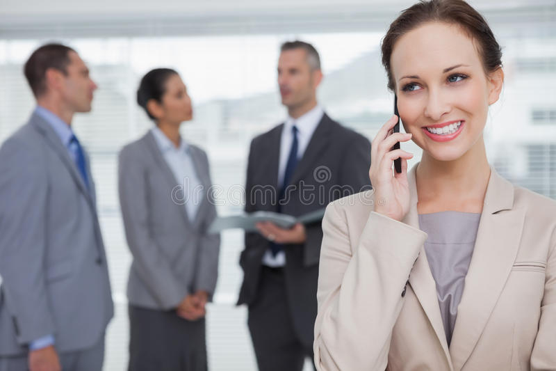Download Smiling Businesswoman Calling While Colleagues Talking Together Stock Photo - Image of chatting, dialing: 33052000
