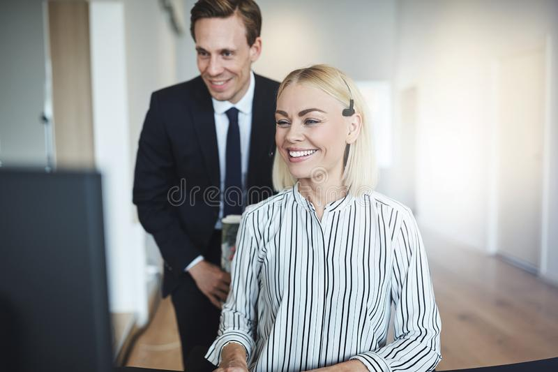 Smiling businesswoman and a colleague working at an office desk stock photo