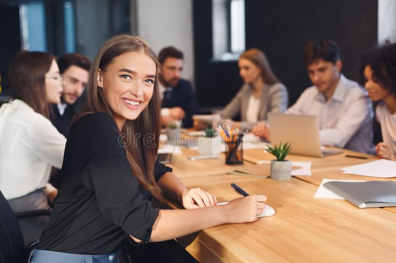 Smiling businesswoman with colleagues working on background stock photography