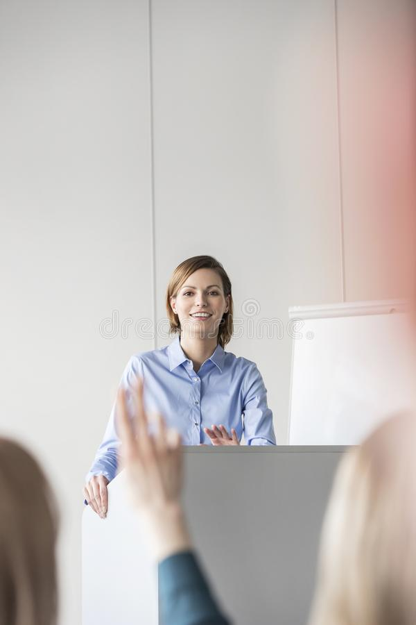 Smiling businesswoman communicating with colleagues in conference stock photography
